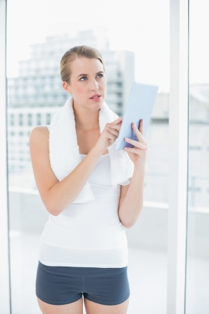 Pensive sporty woman in bright sports hall using tablet pc photo