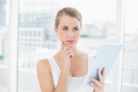 Pensive sporty woman in bright sports hall using tablet computer photo