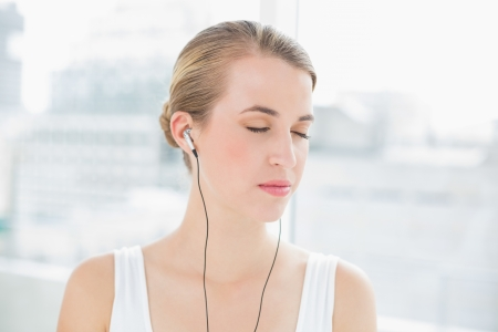 Head shot of relaxed sporty woman in bright sports hall listening to music photo