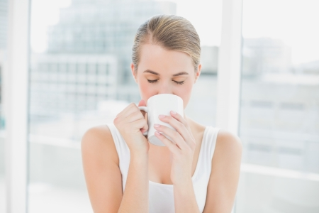 Blond woman in bright room drinking coffee photo