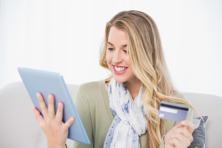 Cheerful pretty blonde in bright living room using her credit card to buy online Stock Photo - 22324053