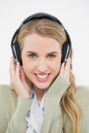 Smiling cute blonde in bright living room listening to music photo
