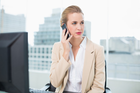 Serious attractive businesswoman on the phone in bright office photo