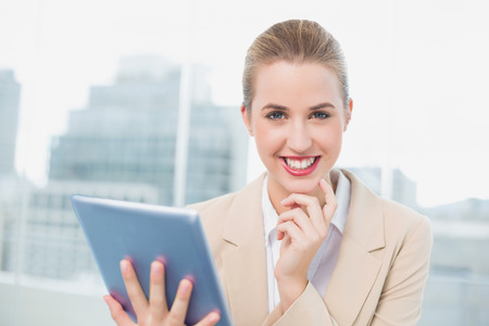 Happy attractive businesswoman in bright office using her tablet photo