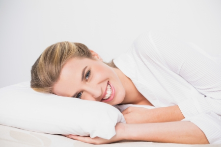 Smiling cute model lying on cosy bed in bright bedroom photo