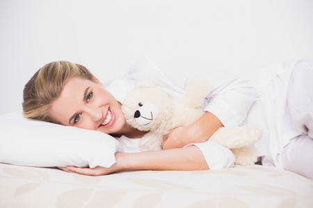 Cheerful cute model lying on cosy bed in bright bedroom with teddy bear photo