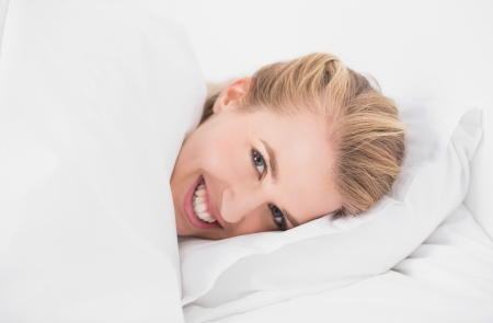 Smiling pretty model relaxing in cosy bed in bright bedroom photo