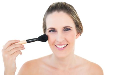 Cheerful woman using blusher brush posing on white background photo