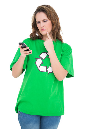 Thoughtful environmental activist looking at her phone against white background photo