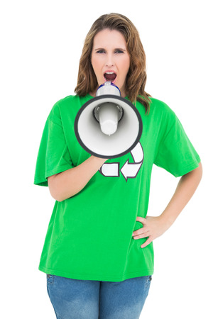 Environmental activist holding and shouting on megaphone against white background photo