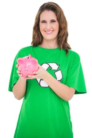 activist: Smiling environmental activist showing piggy bank against white background