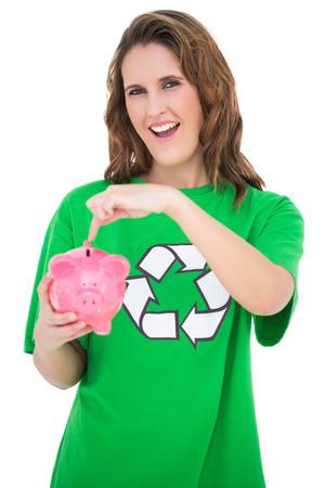 activist: Environmental activist pointing at piggy bank against white background