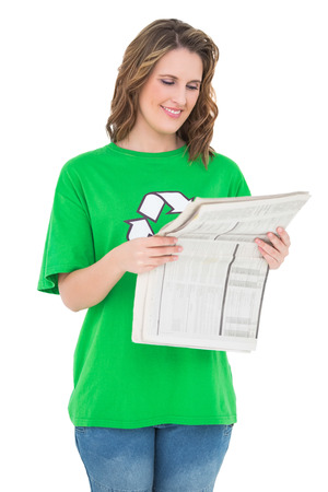 Smiling environmental activist reading newspaper against white background photo