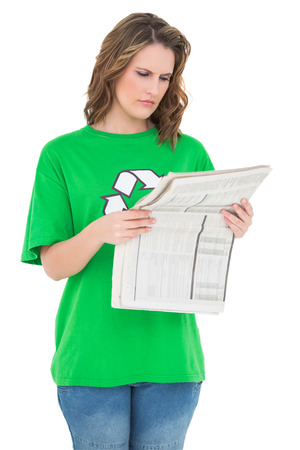 Concentrated environmental activist reading newspaper against white background photo