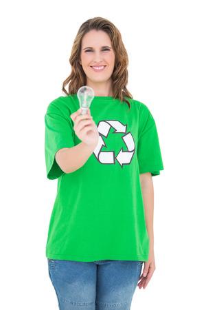 activist: Smiling environmental activist holding light bulb against white background