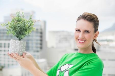 activist: Smiling activist holding plant looking at camera Stock Photo