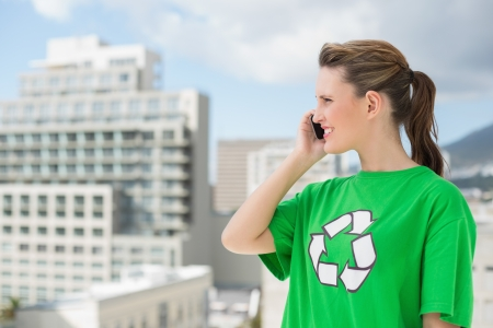 Woman wearing green recycling tshirt talking on the phone outside on a sunny day Stock Photo - 22324361