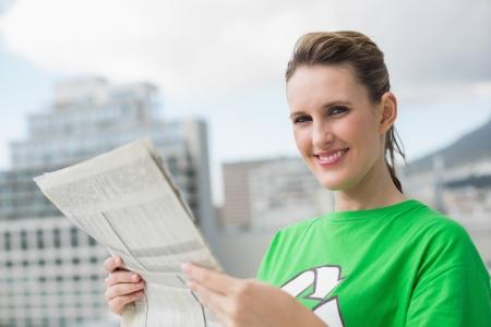 Environmental activist holding newspaper and smiling at camera Stock Photo