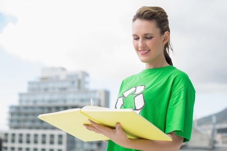 activist: Smiling activist with recycling tshirt reading outside on a sunny day Stock Photo
