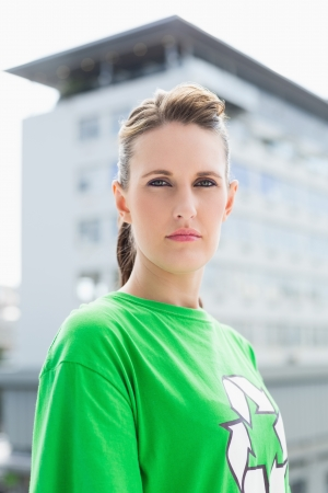 balcony view: Unsmiling woman wearing green shirt with recycling symbol looking at camera