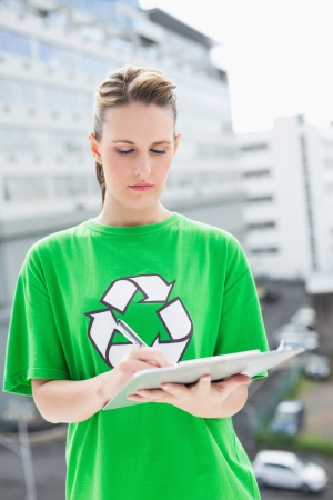 activist: Concentrated environmental activist writing on clipboard
