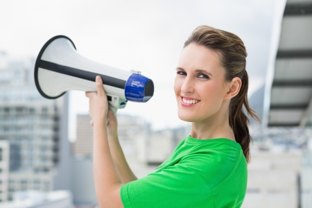 Smiling woman holding megaphone looking at camera photo