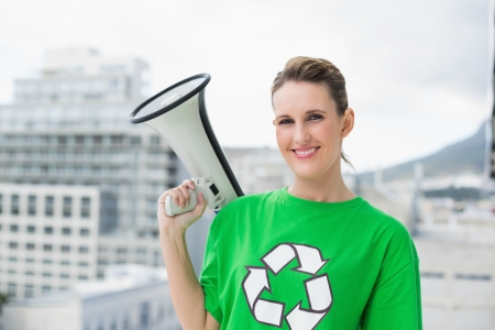 Smiling woman wearing recycling tshirt holding megaphone outside on a bright day photo