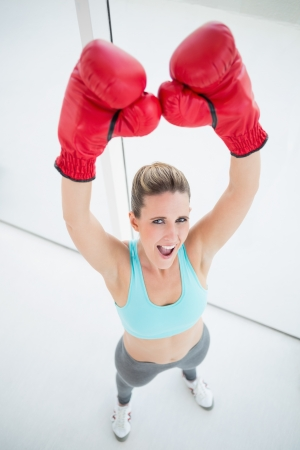Woman with red boxing gloves arms up and screaming photo