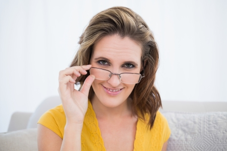 Attractive woman wearing glasses sitting on sofa looking at camera photo