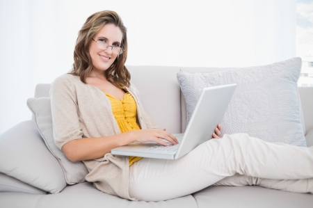 Smiling gorgeous model using laptop on cosy sofa looking at camera photo