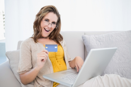 Happy woman lying on sofa using laptop showing credit card photo