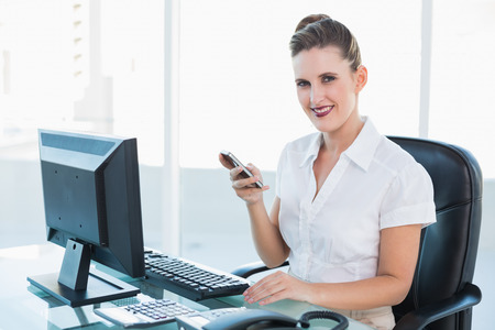 Smiling businesswoman using mobile phone in her office photo