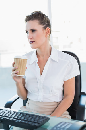 Thoughtful businesswoman holding coffee in bright office photo