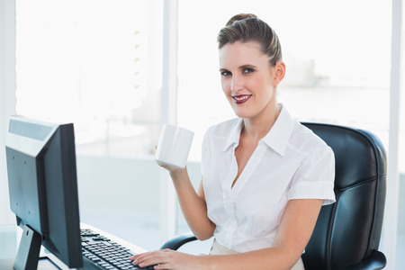 Happy attractive businesswoman having coffee in her office photo