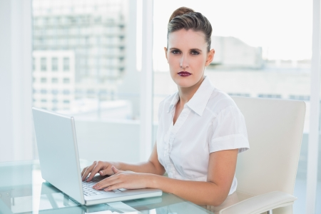 Serious businesswoman working at home on laptop