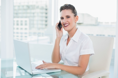 Happy businesswoman talking on the phone while looking at camera at home photo