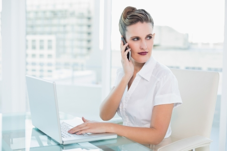 Stylish businesswoman talking on the phone at home photo