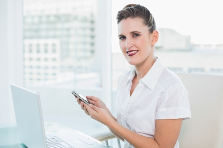 Smiling businesswoman using phone at home looking at camera photo