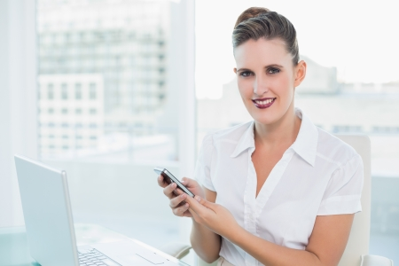 Cheerful gorgeous businesswoman using phone in bright office photo