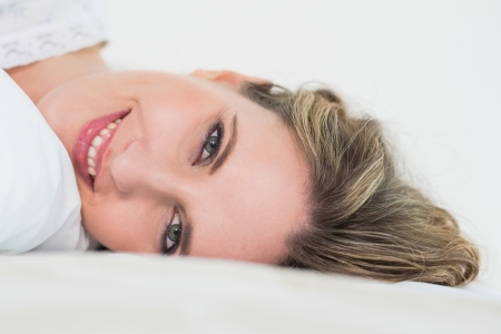 Close up of smiling pretty blonde woman in cosy bed resting photo