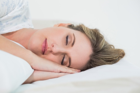 Attractive blonde woman sleeping in cosy bed photo