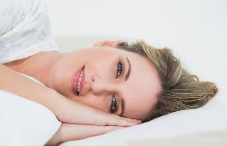Smiling gorgeous blonde woman sleeping in cosy bedroom photo
