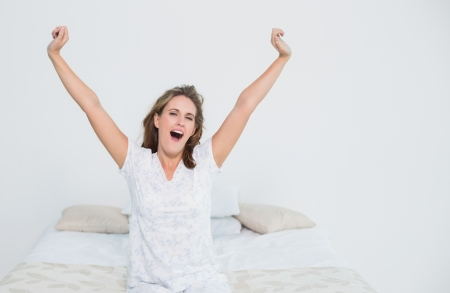 Pretty woman in bed stretching when waking up Stock Photo