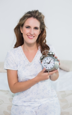 Smiling woman sitting on bed holding alarm clock looking at camera photo