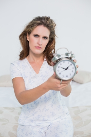 unsmiling: Frowning tired woman in bright bedroom showing alarm clock