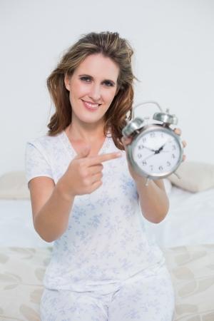 Smiling woman sitting on bed pointing at alarm clock looking at camera photo