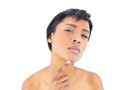 mujeres negras desnudas: Pensativo mujer de pelo negro posando con un dedo en la barbilla sobre fondo blanco