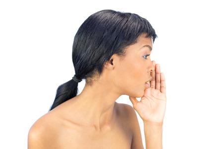 mujeres negras desnudas: Atractiva mujer de pelo negro que susurra un secreto en el fondo blanco Foto de archivo
