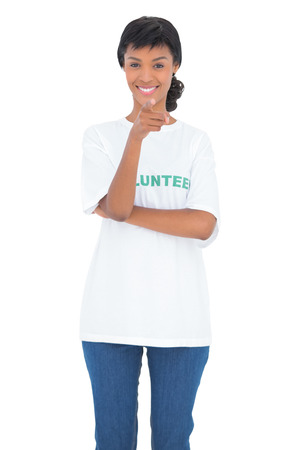 volunteer point: Cheerful black haired volunteer pointing the camera with her finger on white background