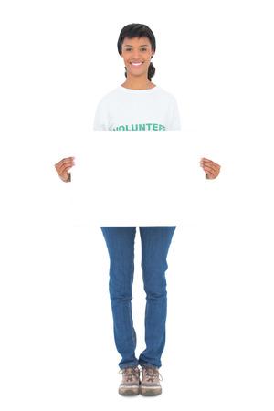 altruism: Encantado voluntario pelo negro con un panel en blanco frente a la cámara sobre fondo blanco